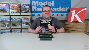 Cody Grivno holds Tony Koester's Applying Lessons from the Prototype book, with ScaleTrains.com HO scale Burlington Northern green and black SD45 in front, RailSmith Models N scale Great Northern Big Sky Blue streamlined coach in front of that