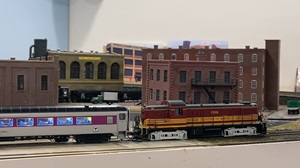 A locomotives pulls a train of Rapido 8600 series coach cars around a model railroad layout.